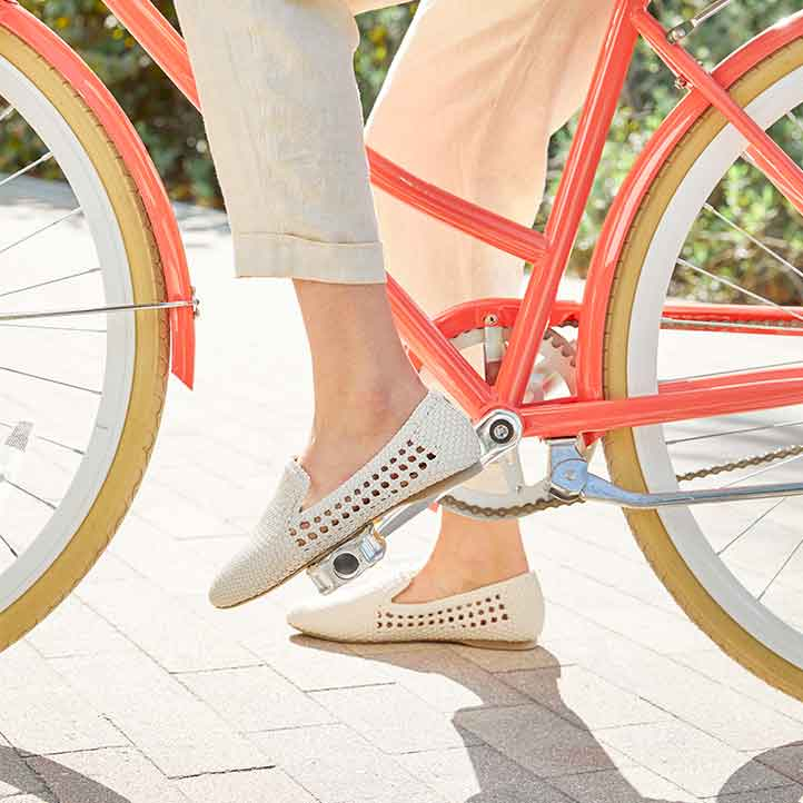 woman on a bike wearing white handwoven vegan leather flats