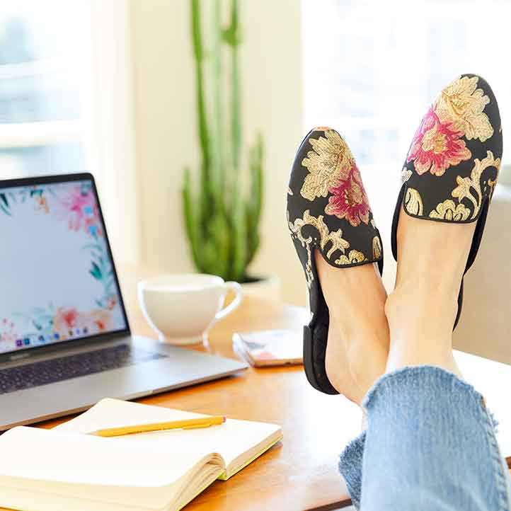 woman with feet up wearing vegan floral jacquard slides