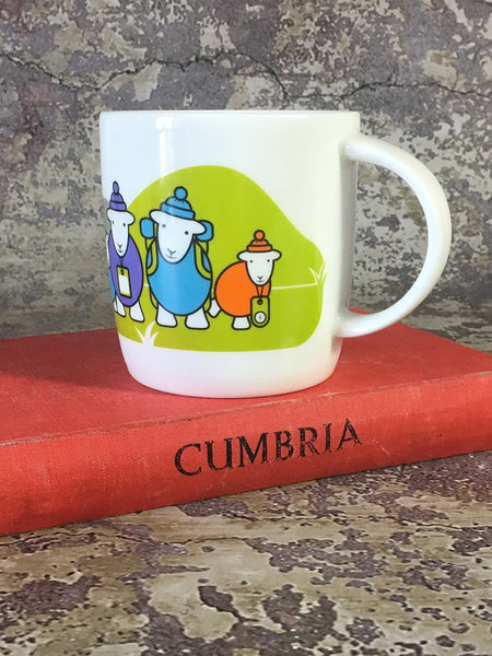 White mug with drawing of three Herdy sheep placed on a Cumbria book