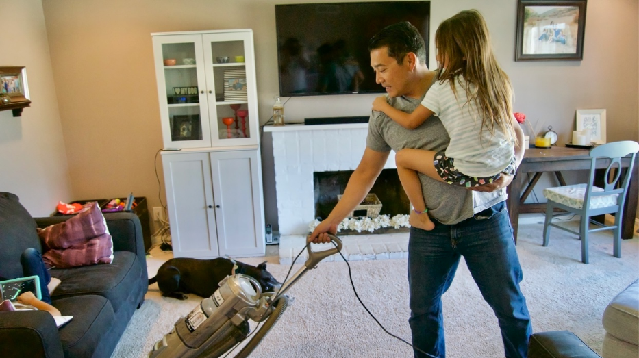 dad vacuuming with baby
