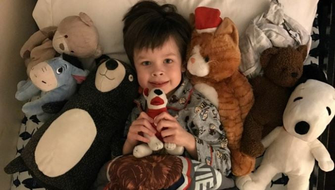 kid with toys on bed