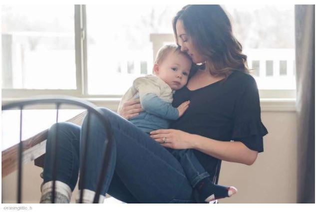 mom holding baby in arms on chair