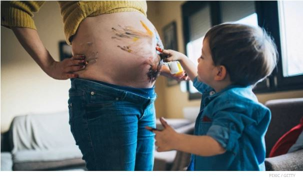 toddler drawing on mom pregnant tummy