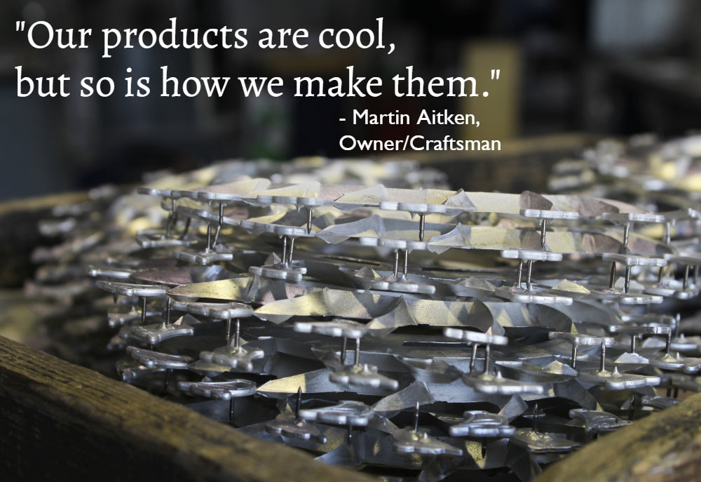"tray of freshly cast pewter sits in the workshop with a quote on the image ""our products are cool, but so is how we make them"" martin aitken fredericton pewter"