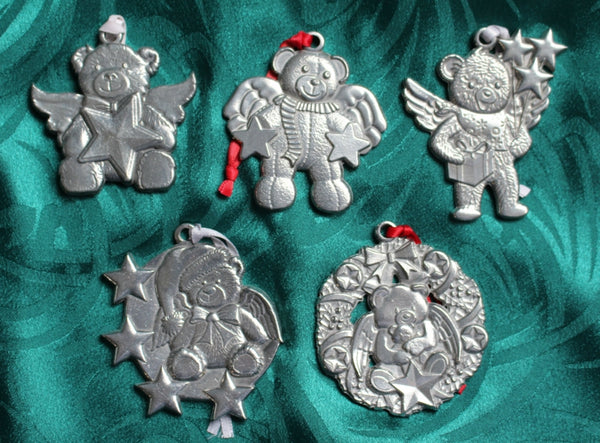 Five pewter ornaments, each featuring a bear, angel wings, and stars, laid on green silk.