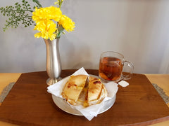 a wooden tray shows a breakfast bagel on a pewter plate beside a glass mug of tea. a pewter vase holds yellow flowers