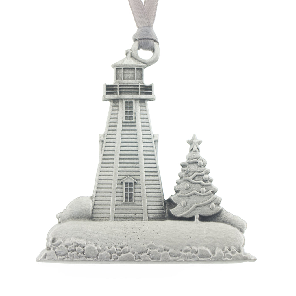 A bucolic scene of a lighthouse with a Christmas tree on a snow covered shore. Peggy's Cove. Christmas Tree ornament. Made from Pewter. Silver ribbon. Made in Fredericton NB New Brunswick Canada