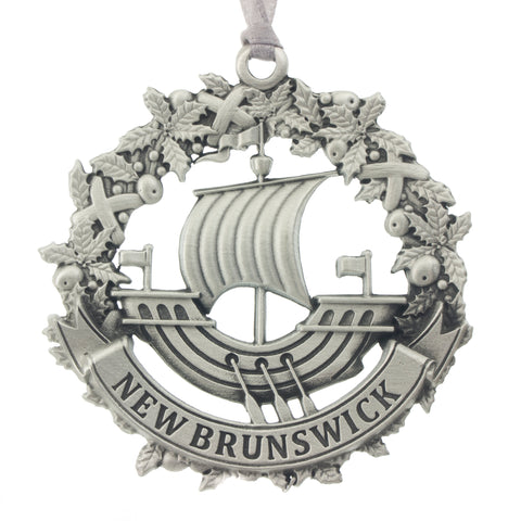 The NB galley inset in a wreath, and a New Brunswick Banner. Christmas Tree ornament. Made from Pewter. Silver ribbon. Made in Fredericton NB Canada
