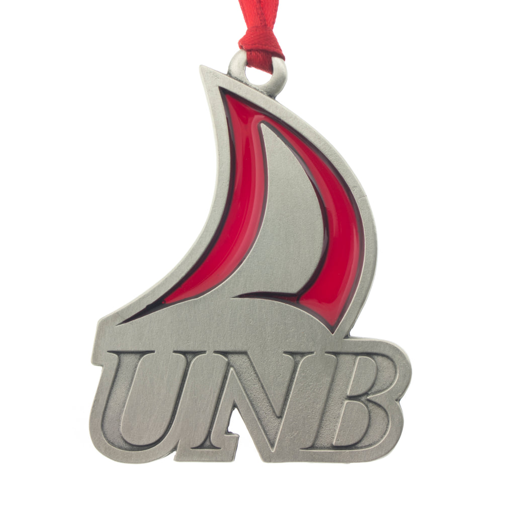 The UNB Logo with a handsome translucent red enamal embellishment. Christmas Tree ornament. Made from Pewter. Red ribbon. Made in Fredericton NB New Brunswick Canada