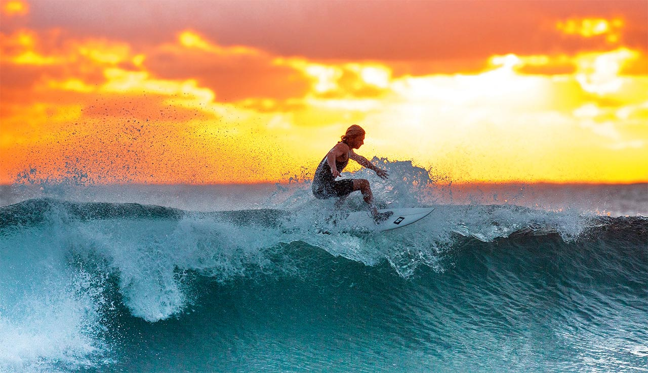 Surfing a wave in the warm ocean during a sunset