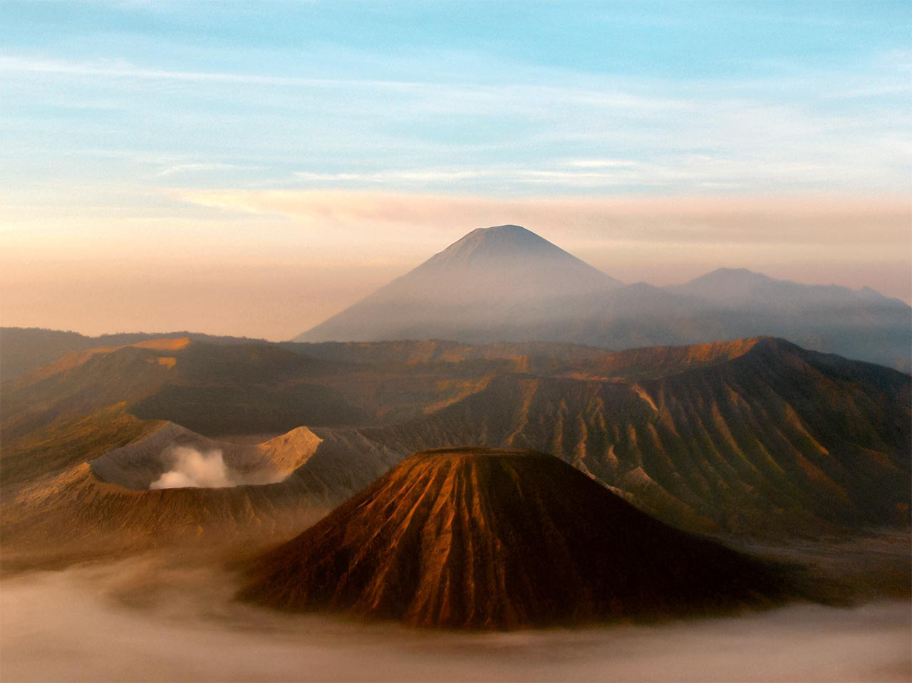 Steam rises from Mount Bromo's crater (in the foreground). It is one the most active volcanoes in the world. Mount Semeru stands tall at the background.