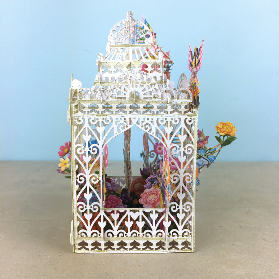 Flower Fairies play amongst flowers in laser cut paper birdcage
