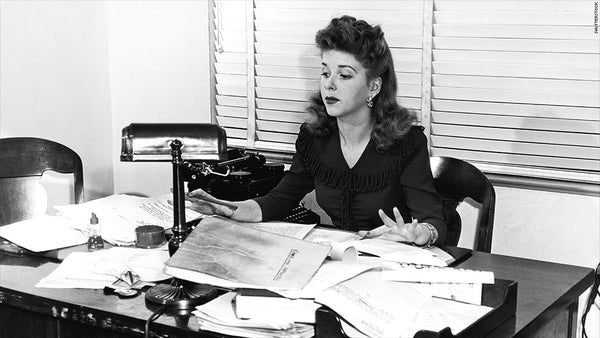 Picture from I Love Lucy sitting at a desk with papers scattered over the desk, unorganized