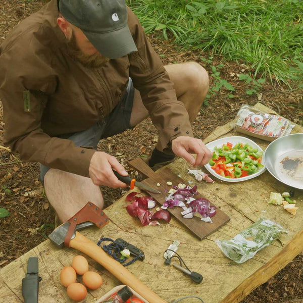 person preparing vegetables for cooking in the woods