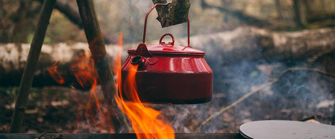 Red kettle over campfire