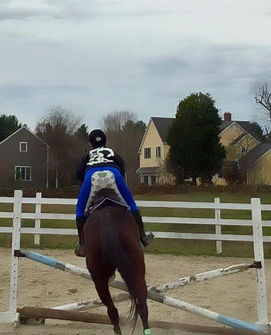 Another satisfied customer and her horse jump a course in Buckwild's blue and argyle full seat riding jodhpurs
