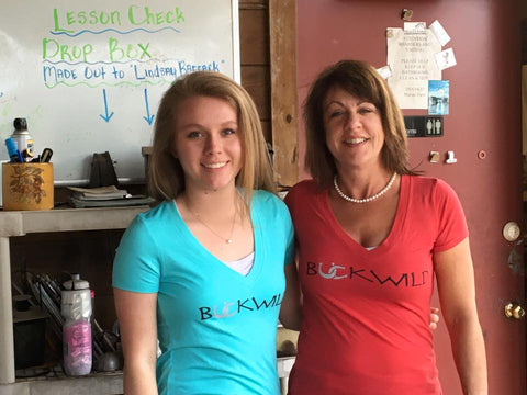 Two happy customers wearing their Buckwild signature v-neck riding tees in light blue and red with Buckwild logos