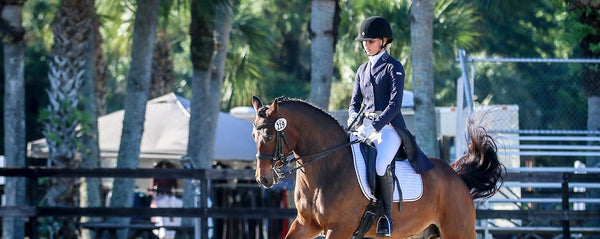 Jamie riding her horse Helios in a Dressage test wearing the Buckwild Signature White Breeches with black full seat