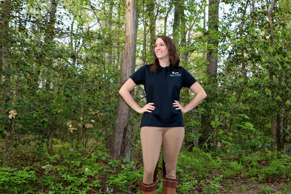 View - Women's tan breeches with brown knee patches. Model wears breeches with tall brown boots and black ladies riding polo shirt while standing on a trail with trees.