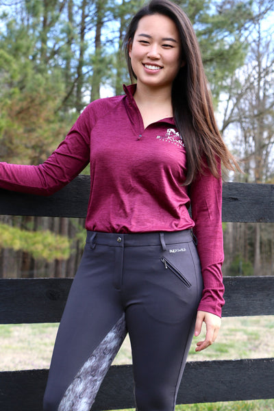 Model wears womens Performance Pull Over with Quarter Zip and long sleeves paired with gray and dapple full seat breeches while leaning on a fence