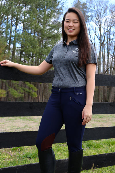 Gray Fitted Women's Polo Shirt with Buckwild Logo. Model in photo pairs navy blue and brown knee patch breeches from Spring 2017 lineup with gray polo while standing by a fence.
