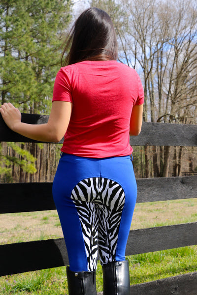 Back view: Model wears Women's Red V-Neck Tee with Buckwild Logo with zebra print paired with royal blue zebra print riding breeches