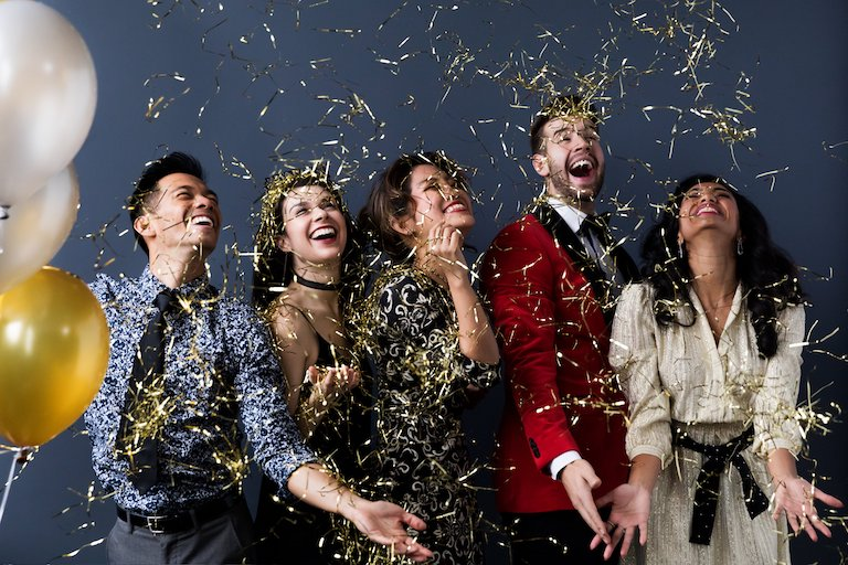 A photo of 3 women and 2 men celebrating. Gold confetti showers down on them.