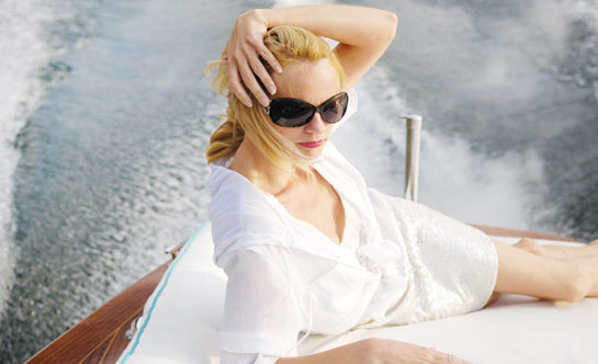 Woman lounges on a sailboat during a sailing weekend trip.