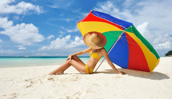 A woman sits under an umbrella on the beach adhering the summer skin care advice from Dr. Noelle Sherber.