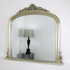 An overall view of this highly decorative, ornate overmantle mirror in a typical setting.