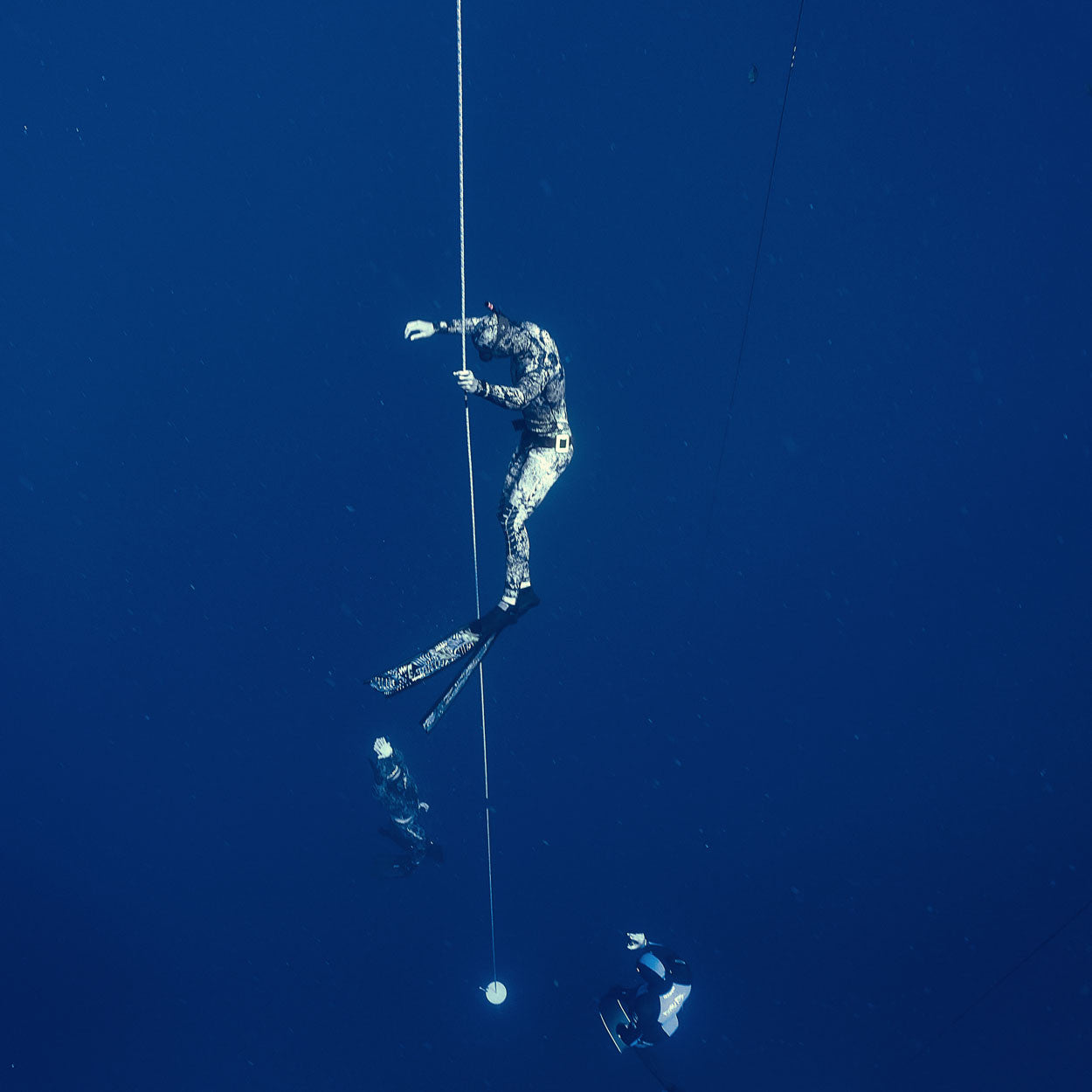 Freediver on deep safety while instructor follows L2 student