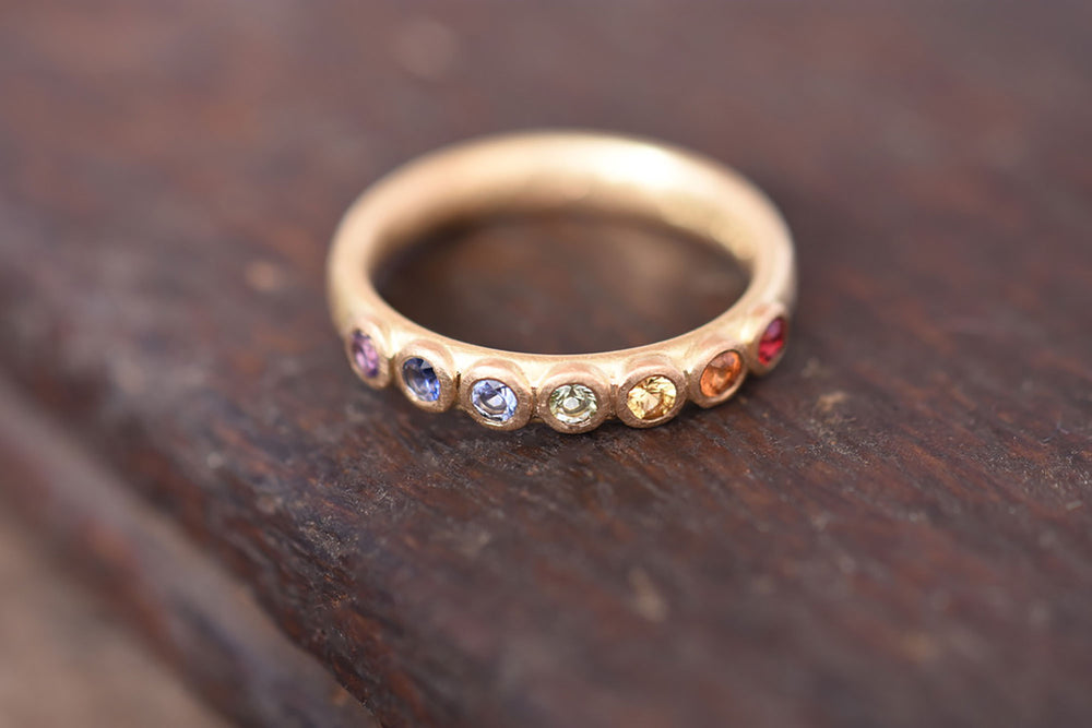 Large rainbow sapphire eternity ring made by Goodman Morris.