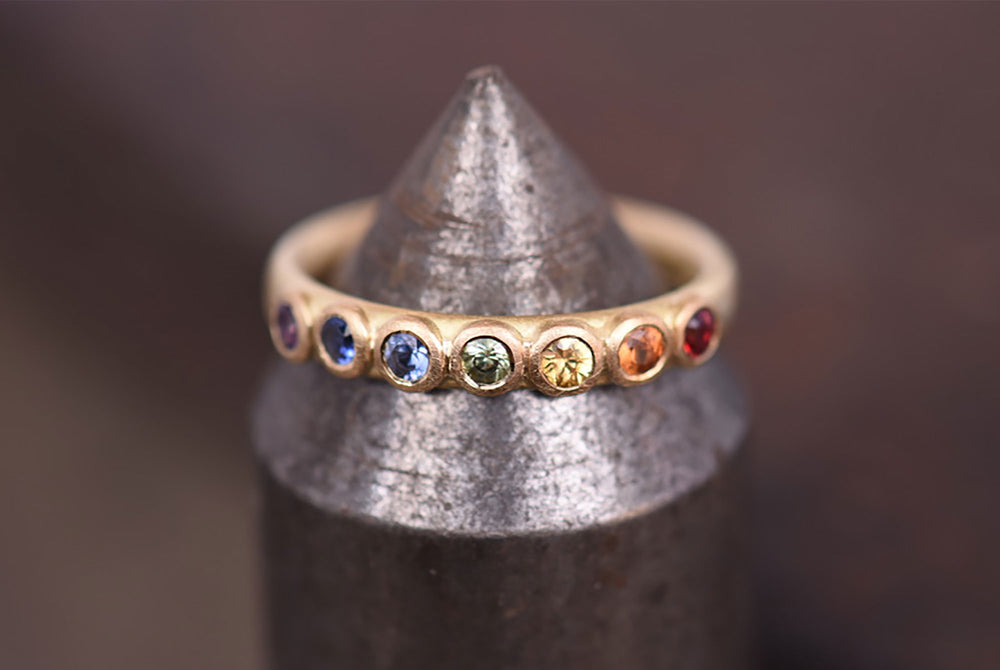 Large rainbow sapphire eternity ring. Made by Goodman Morris.