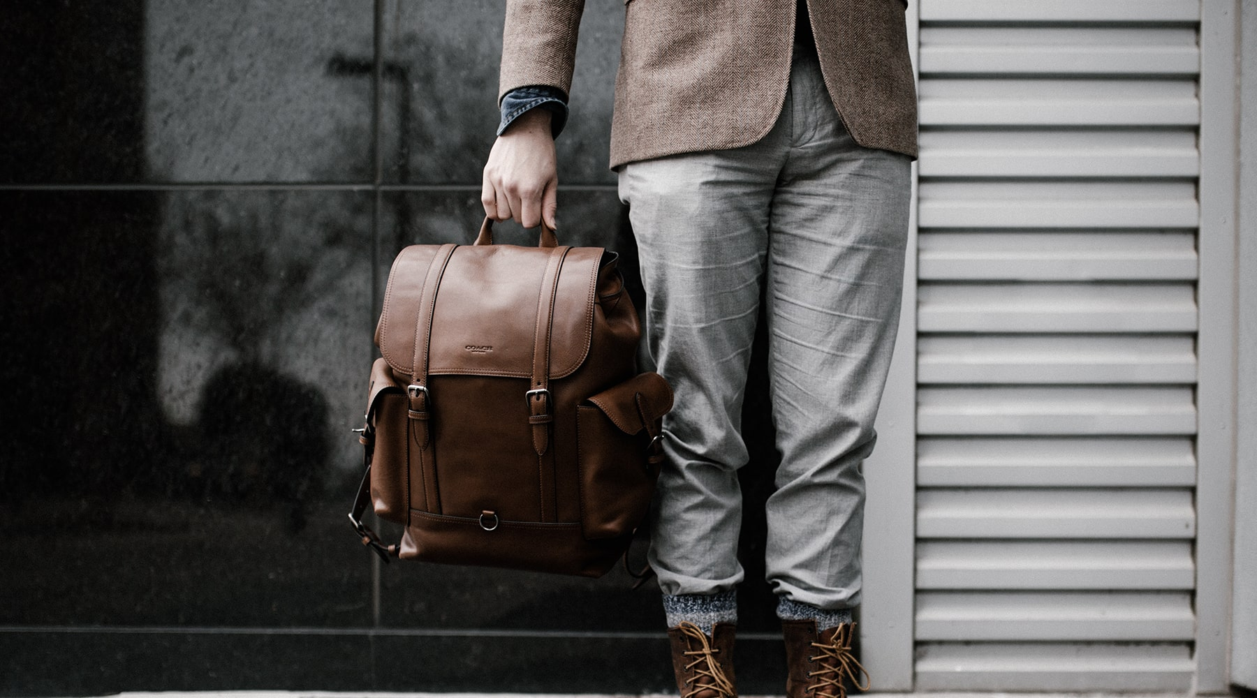 man-holding-leather-backpack