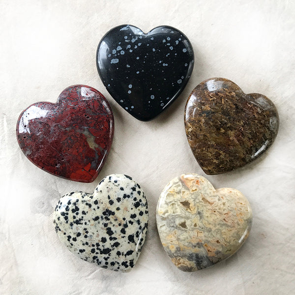 Set of five polished crystal hearts in linen pouch