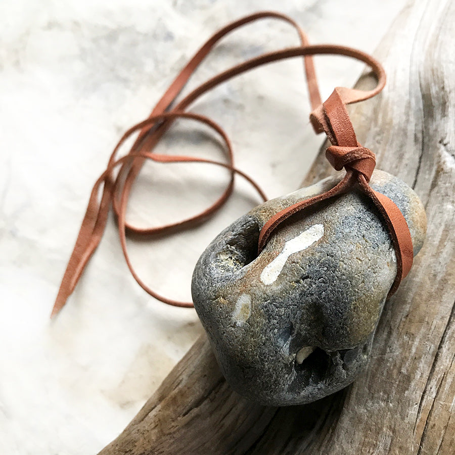 Flint hagstone ('holey' stone) with soft brown leather ribbon