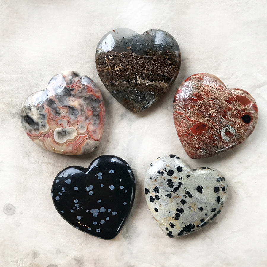 Set of five polished crystal hearts in black leather pouch