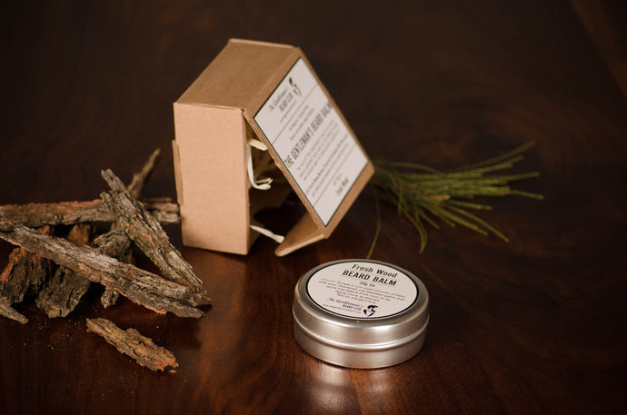 Beard balm tin laying flat on surface with square brown box in the background