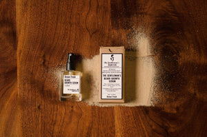 Beard growth serum bottle alongside a cardboard box laying flat on a wooden table with beach sand