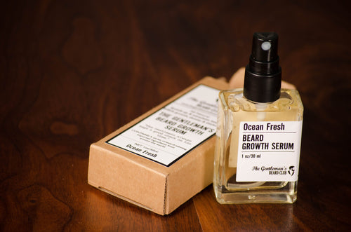 Glass bottle of beard growth serum with black spray pump standing upright on a wooden surface