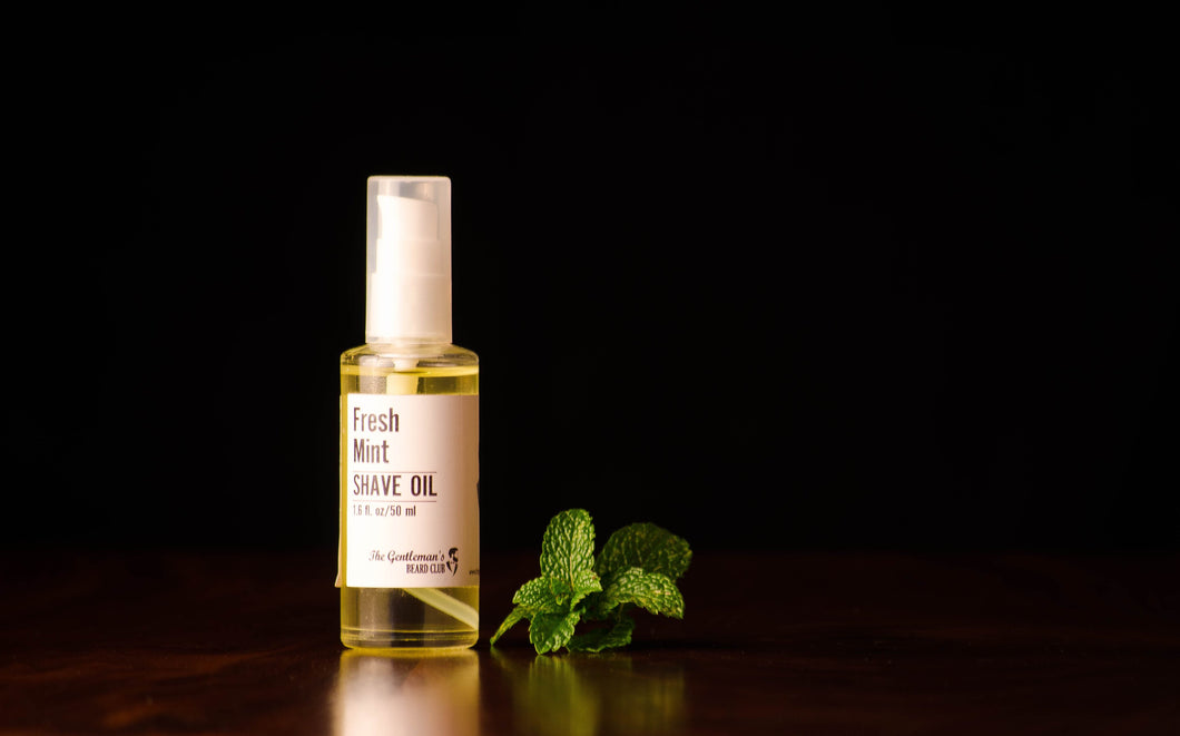 Clear glass bottle containing shaving oil standing alongside a bunch of mint leaves