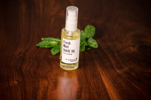 Transparent bottle of shave oil in front of green mint leaves on a wooden table