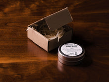 Tin of beard balm laying flat on a wooden surface with an open brown packaging box in the background