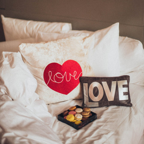 white pillows with two love cushions and a plate of biscuits on a bed