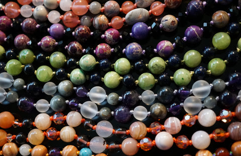 Several colorful malas lined up like bones in the spine. These designs are available now on the MMM online shop.