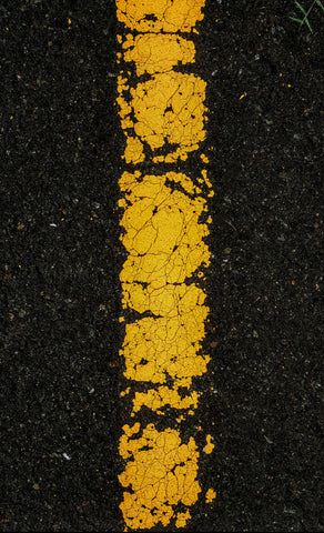 black pavement with painted cracked yellow line