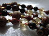 Close up view of beads. 8mm yellow Citrine. DZI Agate. Palmwood framed with faceted gold Czech glass beads. 6mm Goldstone. Faceted black Onyx. Fire red knots between beads.