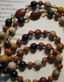 Close up view of 8mm Mookaite Jasper beads; 6mm Goldstone and Blue Tiger Eye; two 10x14 red oval Mookaite Jasper beads framed with light gold crystals mark the quarter and three-quarter mark of the mala. Navy blue sutra (cord) and tassel. Hand-knotted mala.
