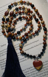 full view of Mookaite Jasper with Heart Mala.  8mm Mookaite Jasper beads in earthy brown, light tan, and reddish hues; 6mm sparkly brown Goldstone beads; dark blue Tiger Eye beads; a few light gold crystal beads highlight the 10x14mm red oval Mookaite Jasper beads that mark the quarter and three-quarter mark of the mala. A heart-shaped Mookaite Jasper pendant is the guru. An optional second guru is an 8mm Goldstone bead. A navy blue tassel flows from the base of this bead.