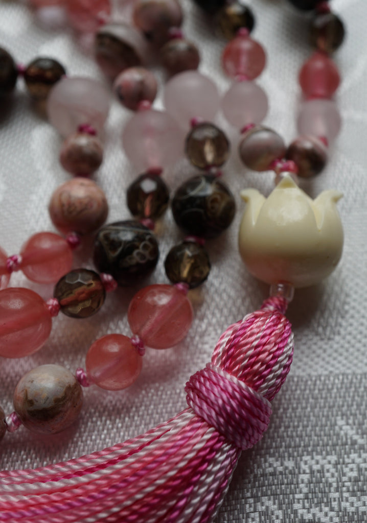 Close up view of 12x15mm antique white resin Lotus Blossom guru and fiesta pink tassel.